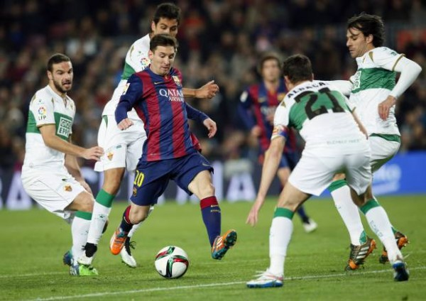 Barcelona's Lionel Messi challenges for the ball against Elche's Edu Albacar and other players during their Spanish King's Cup soccer match at Camp Nou stadium in Barcelona